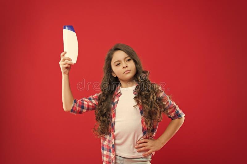Garota de cabelo crespo segurando garrafa de champô Criança pequena no fundo vermelho conceito de Hairdresser salon Shampoo para  fotografia de stock royalty free
