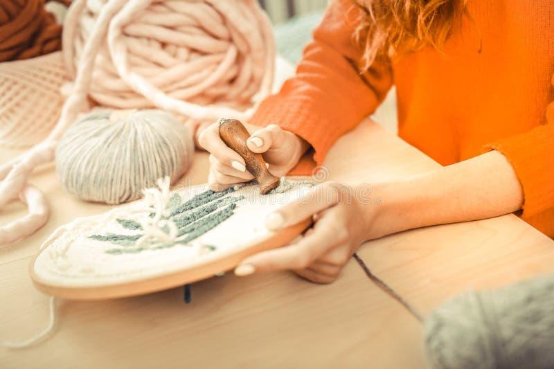 Garota de cabelos vermelhos usando ferramentas profissionais para bordar fotos de stock