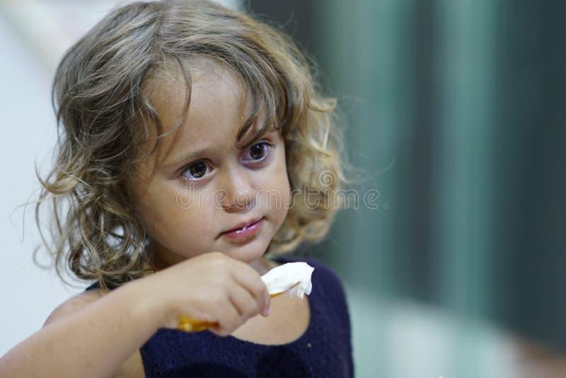 Garota de três anos tomando sorvete durante suas férias em Lefkas fotografia de stock
