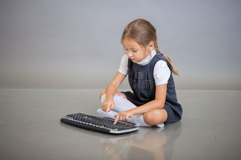 A garota de uniforme escolar se senta sobre fundo cinza e pressiona os botões do teclado do computador imagens de stock royalty free
