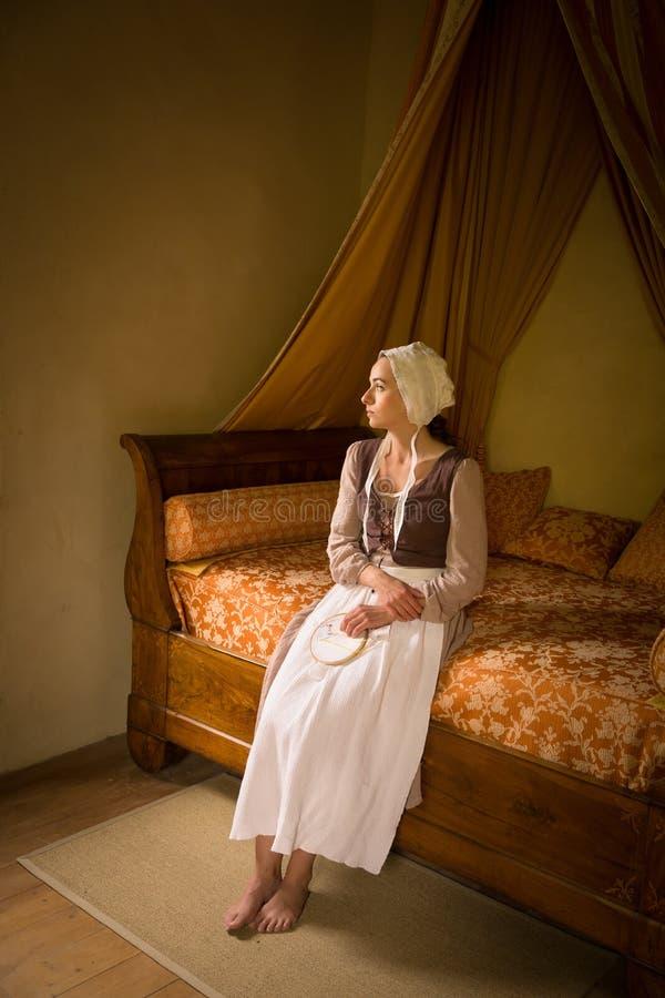 Garota do estilo Vermeer na cama da cobertura fotos de stock