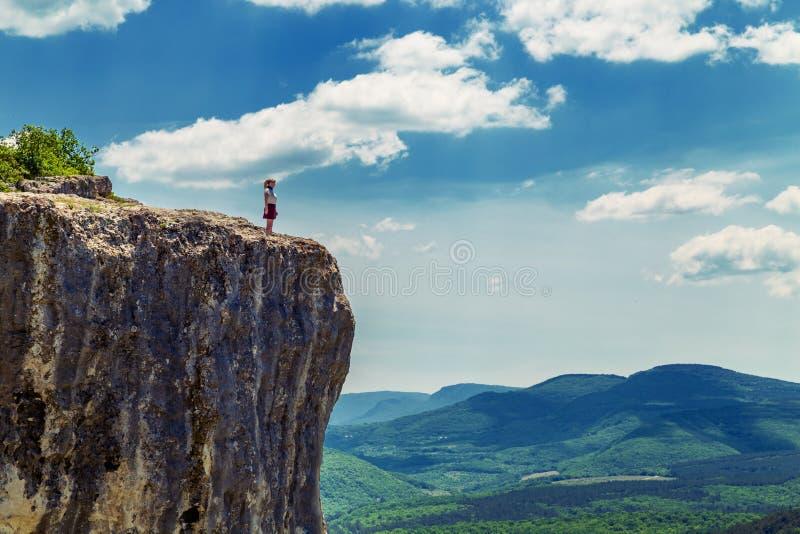 Garota do Hiker fica em cima de uma montanha imagem de stock