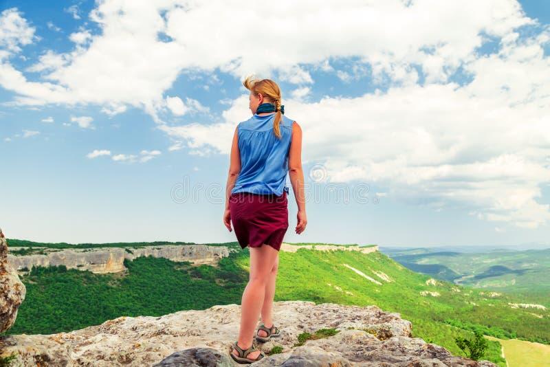 Garota do Hiker fica em cima de uma montanha imagem de stock royalty free