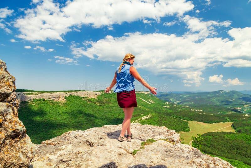 Garota do Hiker fica em cima de uma montanha fotos de stock