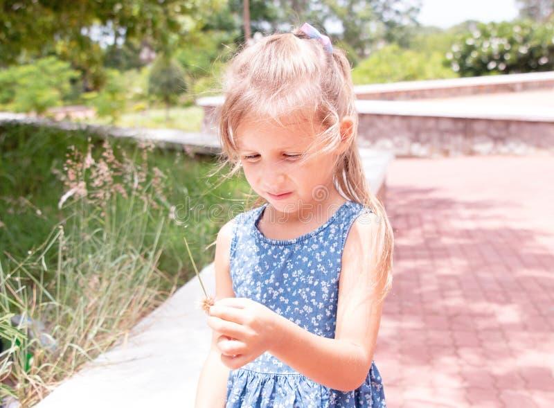 Garota engraçada no parque segura grama da primavera imagem de stock