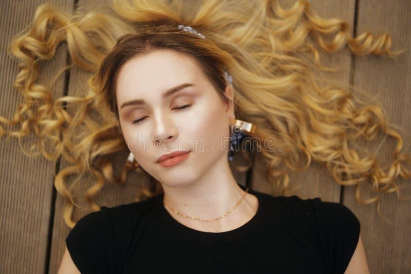 A garota está deitada no píer perto da praia Banho solar feminino Férias de verão, namoradas, viagens, férias com amigos Loira co imagem de stock