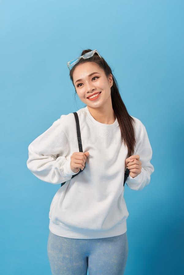 Garota estudante asiática sobre parede azul isolada feliz e sorrindo imagem de stock
