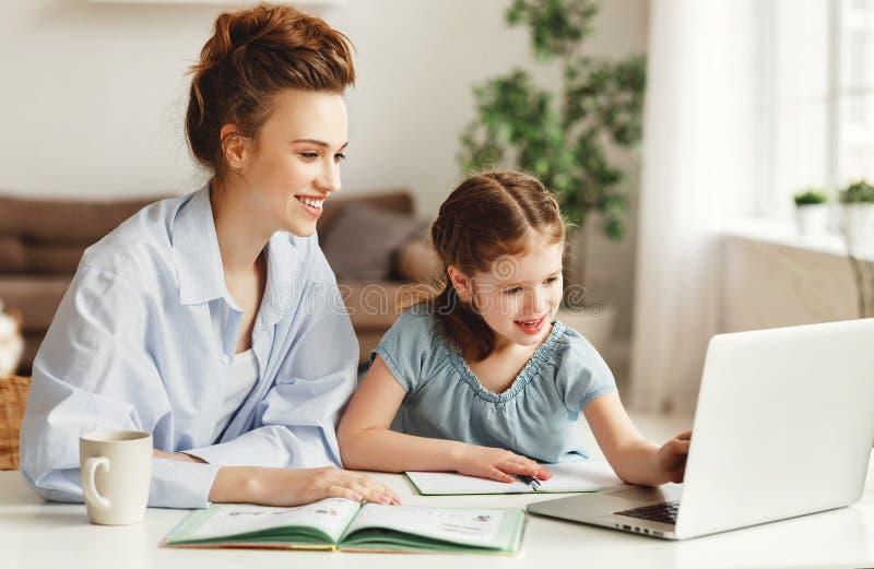 Garota feliz com a mãe estudando online em casa imagens de stock royalty free