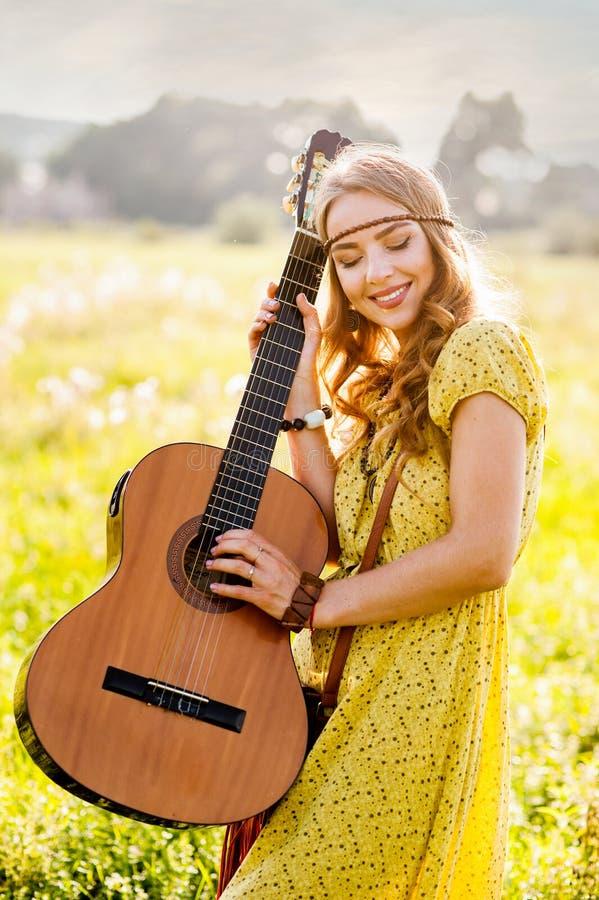 Garota feliz no estilo boêmico de vestido amarelo com guitarra no campo voltou ao pôr do sol fotos de stock