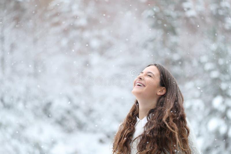 Garota feliz respirando ar fresco desfrutando neve no inverno fotos de stock