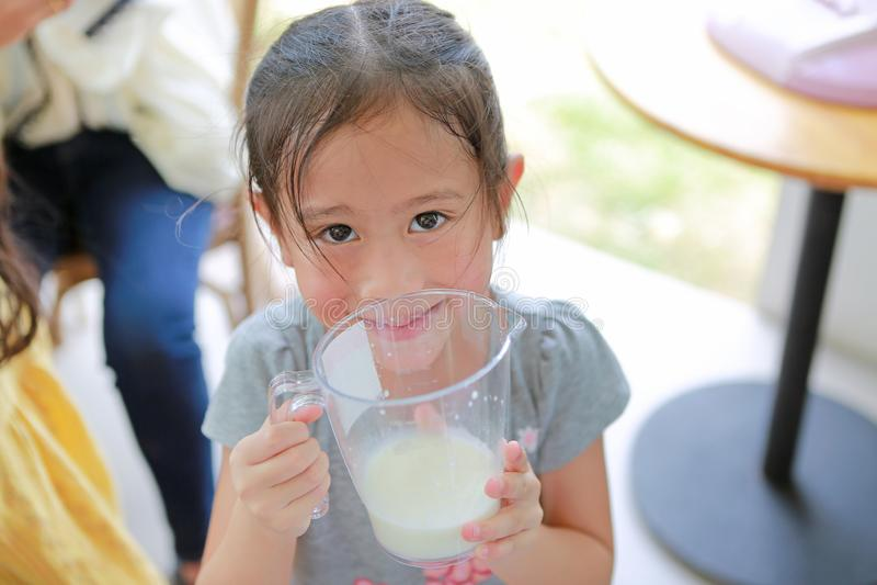 Garota feliz segurando um copo de leite fresco das vacas da fazenda de produção de laticínios fotos de stock royalty free