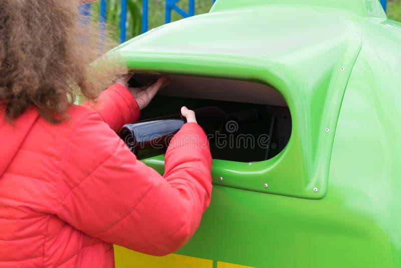 A garota joga uma garrafa de álcool em um recipiente de lixo verde foto de stock