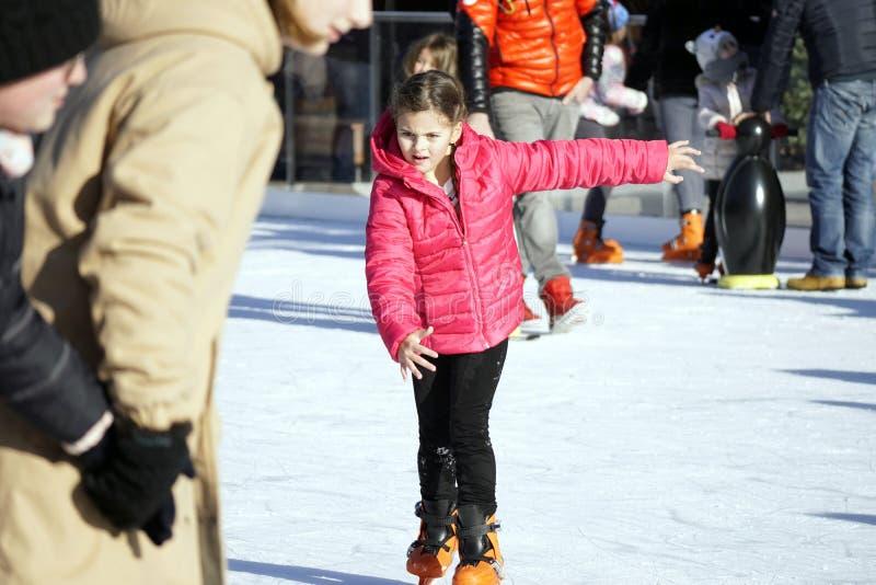 Garota no casaco vermelho patinando no anel de gelo imagem de stock