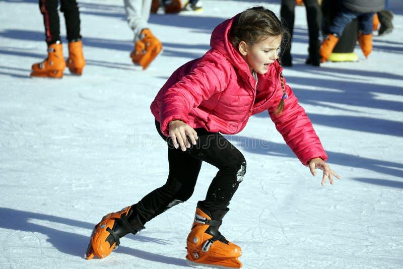 Garota no casaco vermelho patinando no anel de gelo imagem de stock royalty free