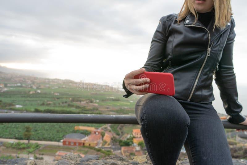 Garota relaxando sentada na cerca em um ponto de vista e telefone celular em suas pernas Curvy Teen se senta no topo da colina em fotografia de stock