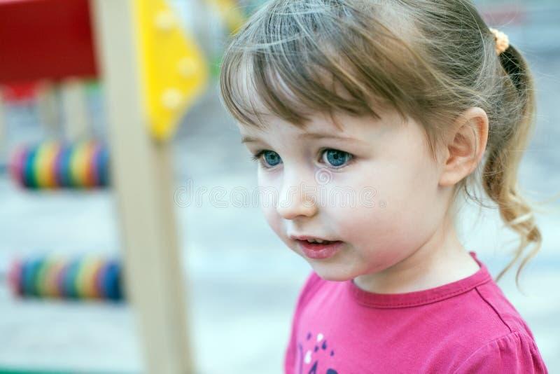 Garota sorridente bonita no plano de fundo do playground externo fotos de stock