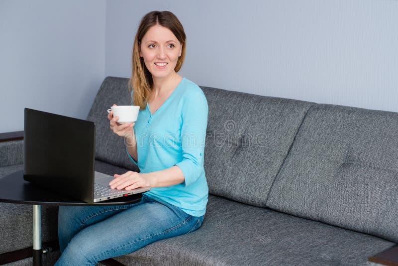 Garota trabalha em casa atrás de um laptop fotografia de stock royalty free