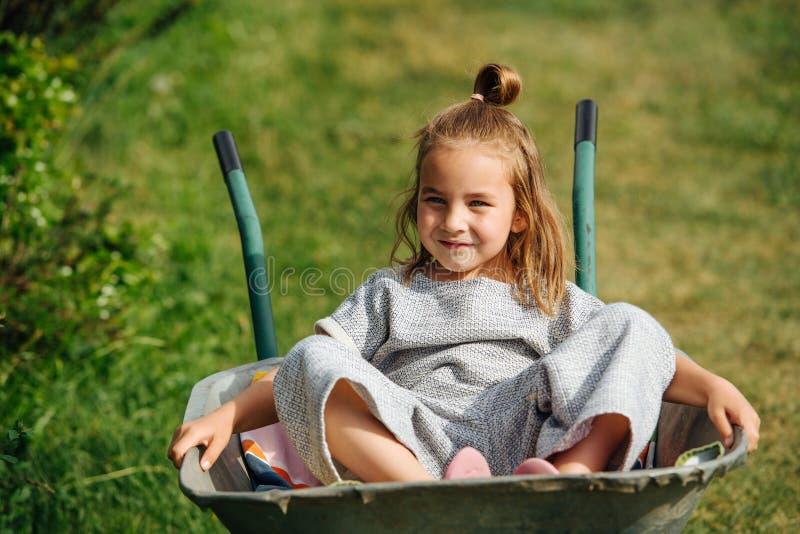 Garotinha bonita sentada confortavelmente em um carrinho de mão num dia quente de verão imagem de stock royalty free