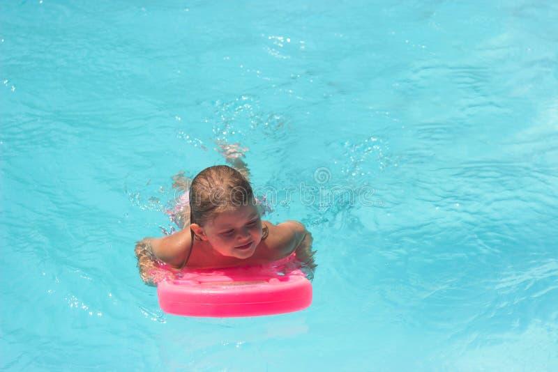 A garotinha na mesa flutuante, aprende a nadar na piscina imagens de stock royalty free