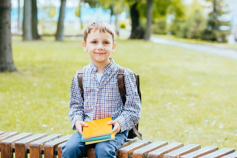 Garotinho bonito sentado no banco no parque ao ar livre no dia do outono Jovem estudante com sua mochila e livros Educação fotos de stock