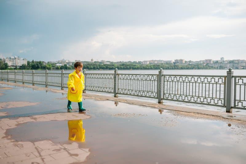 Garotinho brincando no parque chuvoso de verão Criança com guarda-chuva, casaco impermeável e botas pulando em poça e lama na chu foto de stock