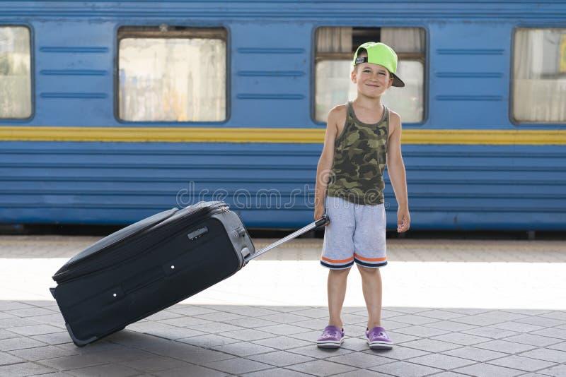 Garotinho feliz com uma mala preta no fundo de um trem azul. Conceito da aventura e do curso fotografia de stock royalty free