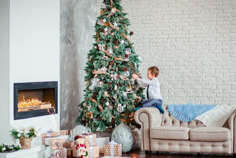Garoto bonito decora árvore de Natal com bolas de Natal, presentes debaixo da árvore de Natal imagem de stock royalty free
