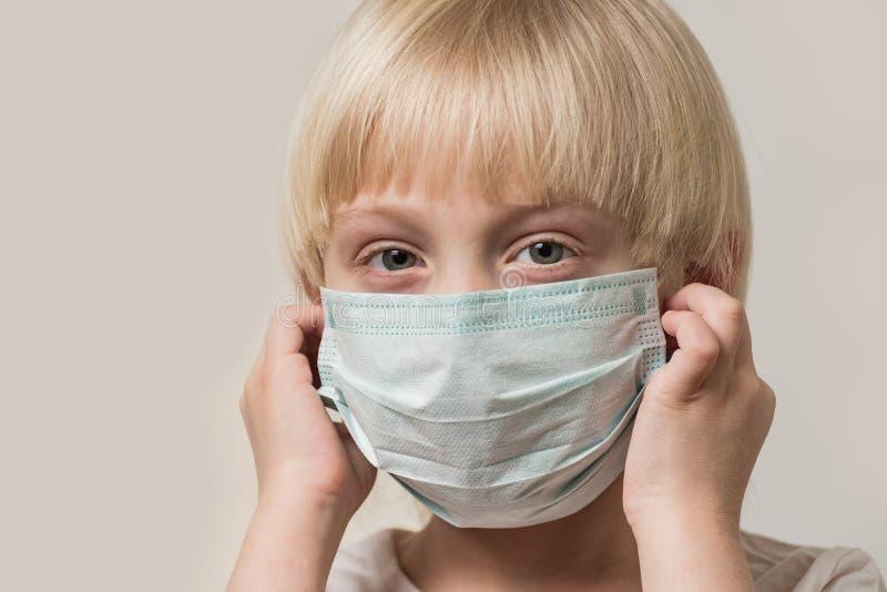 Garoto de cabelo justo usa máscara médica estéril Proteção contra a gripe imagem de stock