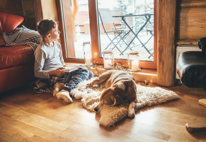 Garoto lendo livro no chão perto de deslizar seu cachorro beagle na pele de ovelha em atmosfera acolhedora de casa Momentos pacíf fotos de stock royalty free