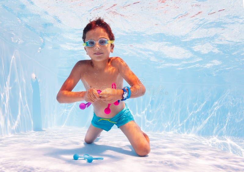 Garoto nadando debaixo d'água leva brinquedos na piscina com óculos imagem de stock