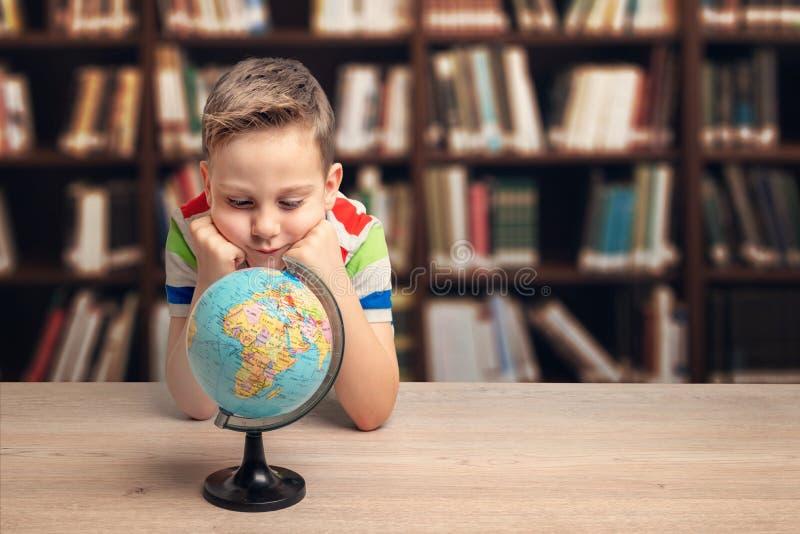 Garoto olha o globo em uma mesa na biblioteca Conceito de geografia de aprendizagem imagem de stock
