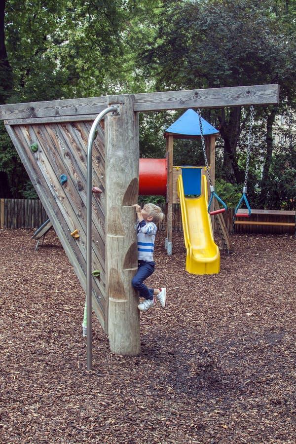 garoto sobe um poste de madeira com passos para deslizar um poste de fogo em um moderno Playground imagem de stock