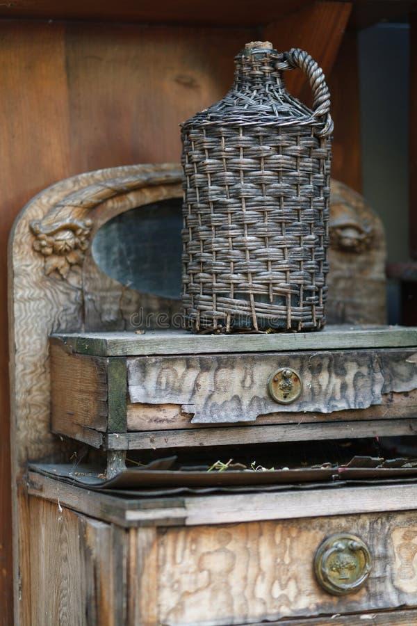 Garrafão na cesta de vime na tabela de madeira imagens de stock royalty free