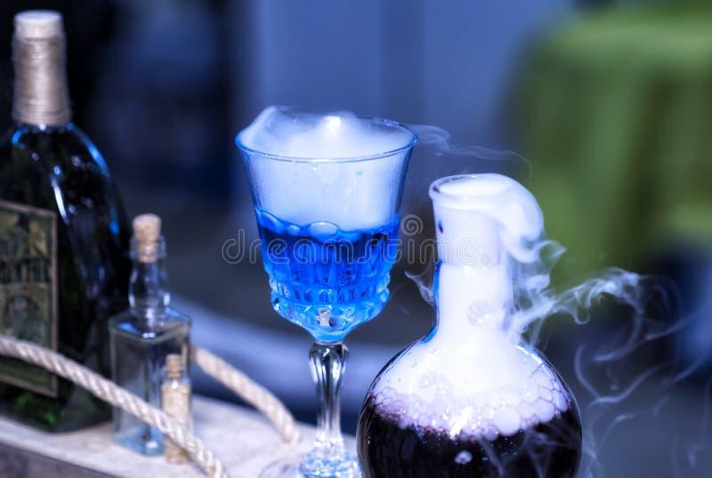 A garrafa azul do fumo que contém bruxas fabrica cerveja, reabastecimento do mana fotografia de stock royalty free