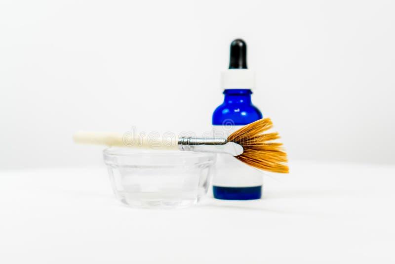 Garrafa azul esbranquiçada para fórmula química cosmética de pele, com pincel de maquiagem de prato e aplicador, para tratamentos imagem de stock