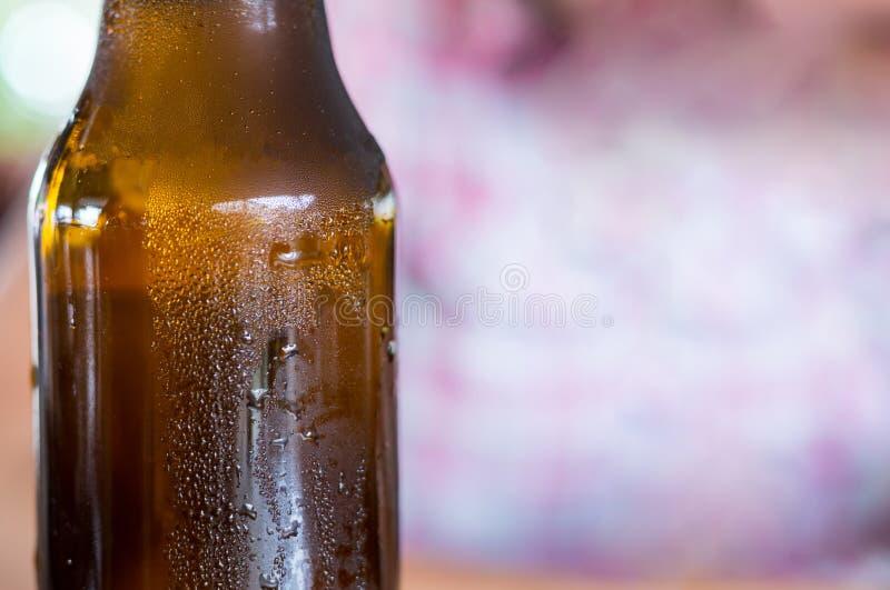 Garrafa baixa do fundo do marrom da cerveja com gotas do orvalho com espaço da cópia no fundo borrado fotografia de stock