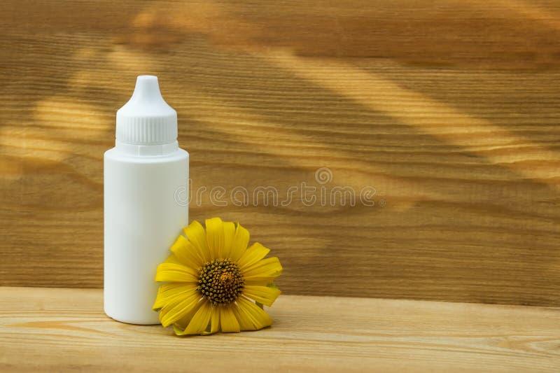 Garrafa branca em um fundo de madeira garrafa e flor amarela Produto cosm?tico natural Massagem dyal do óleo Petr?leo essencial imagem de stock
