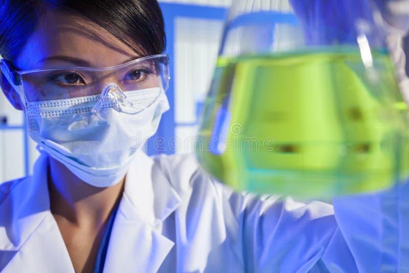 Garrafa chinesa do verde do cientista da mulher no laboratório imagens de stock royalty free