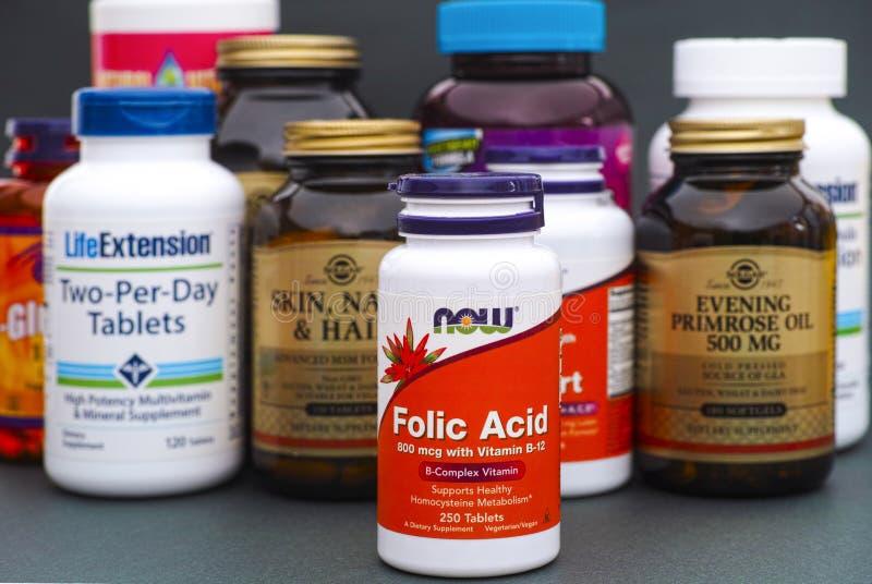 Garrafa com ácido fólico até agora e algumas garrafas com vitaminas e fotografia de stock royalty free