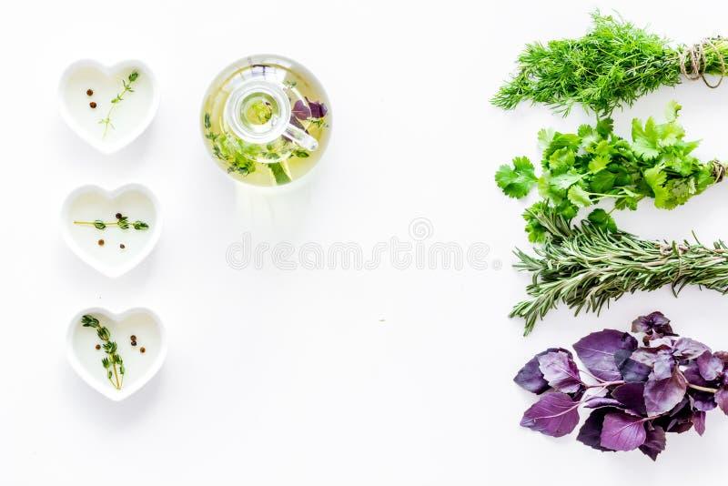 Garrafa com óleo orgânico com os ingredientes das ervas no modelo branco da opinião superior do fundo fotos de stock
