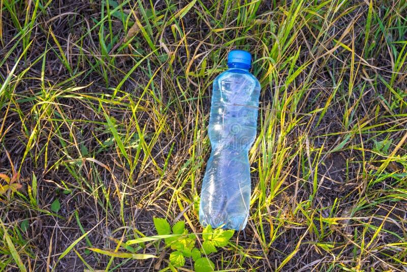 Garrafa com agua pot?vel fresca na grama verde fotografia de stock