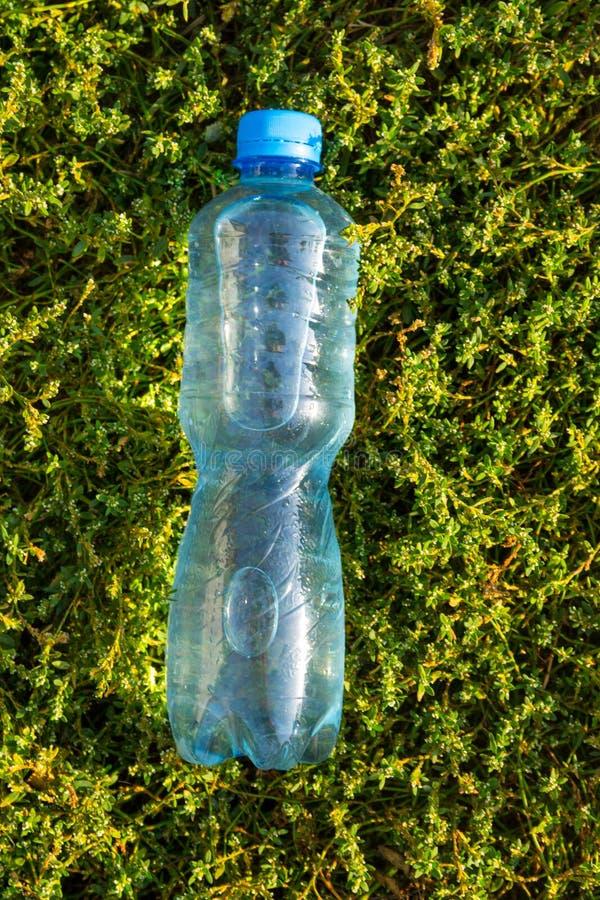Garrafa com agua pot?vel fresca na grama verde imagens de stock
