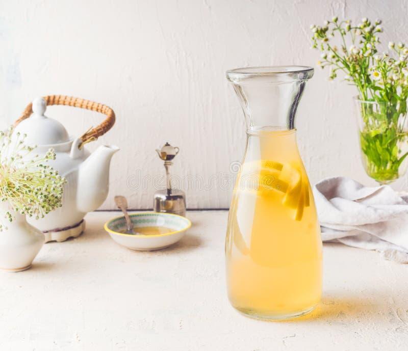 Garrafa com bebida branca da limonada do citrino do chá na mesa de cozinha branca Conceito da bebida do ver?o fotografia de stock royalty free