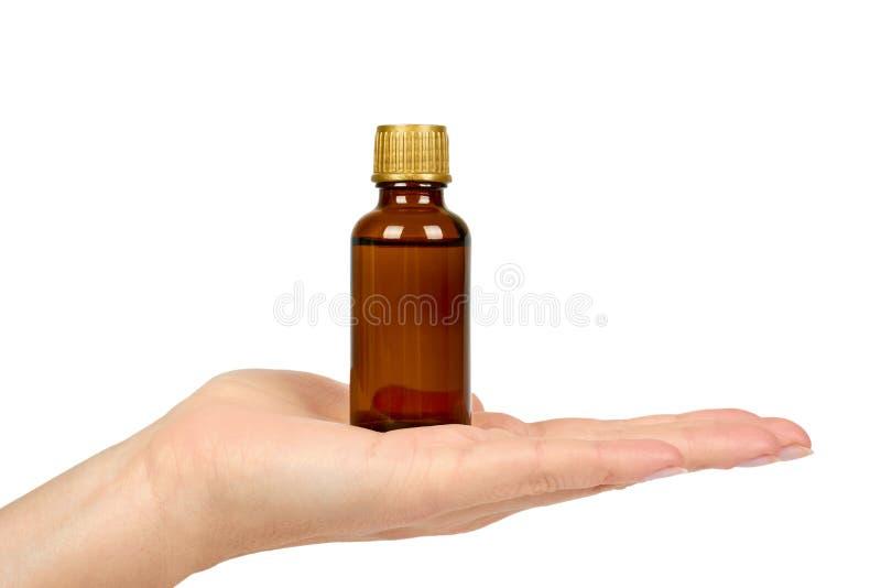 Garrafa com elixir médico, xarope para frios, suspensão antipirética à disposição Isolado no fundo branco Saúde e medicina imagem de stock