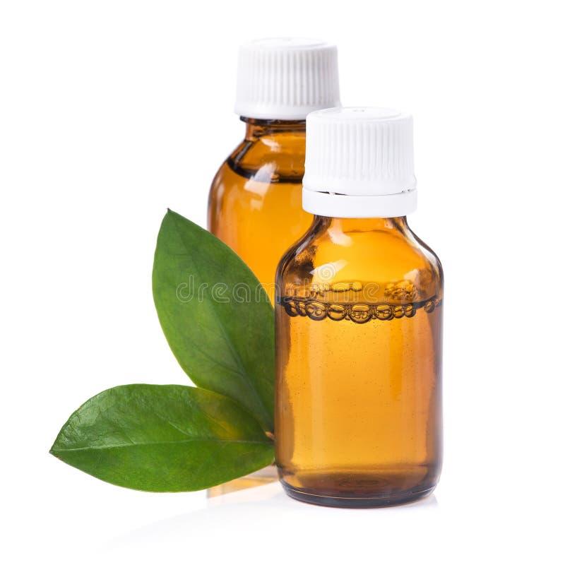 Garrafa com a medicina líquida, os comprimidos e a folha verde isolados imagem de stock