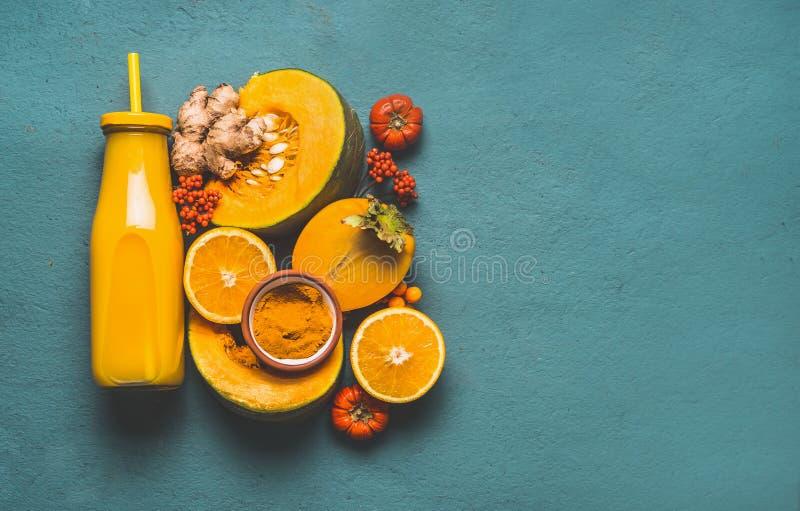Garrafa com o batido energético saudável para a estação fria com os ingredientes alaranjados da cor fotografia de stock