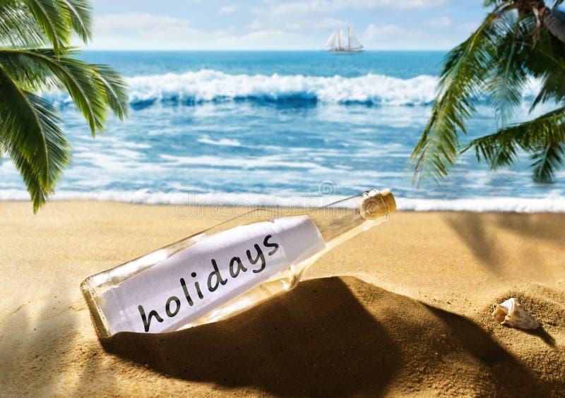 Garrafa com os feriados da mensagem na praia imagens de stock