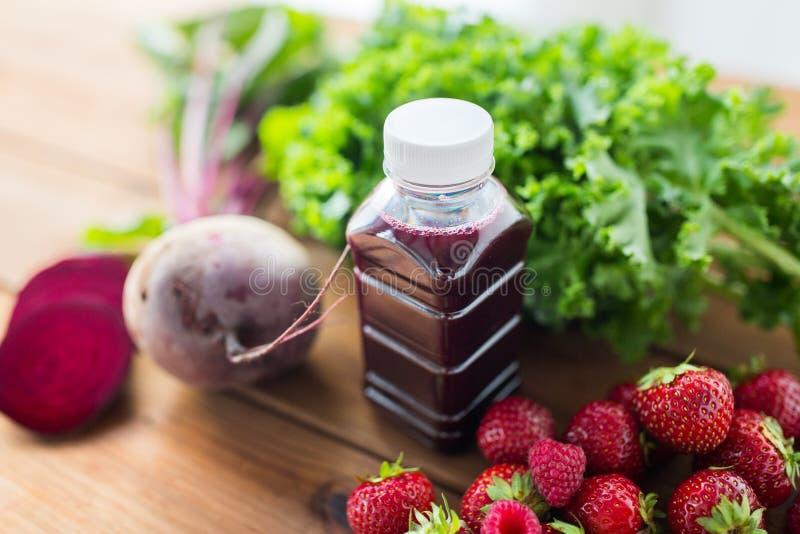 Garrafa com suco das beterrabas, frutas e legumes fotografia de stock