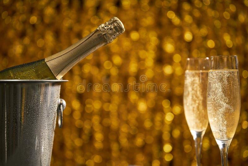 Garrafa completa do champanhe em uma cubeta com gelo e dois vidros do champanhe no fundo dourado do bokeh foto de stock
