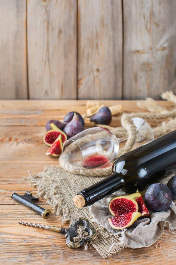Garrafa, corkscrew, vidro do vinho tinto, figos em uma tabela imagens de stock